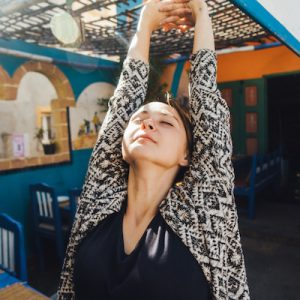 Woman standing on patio of cafe  in blue colors in Morocco