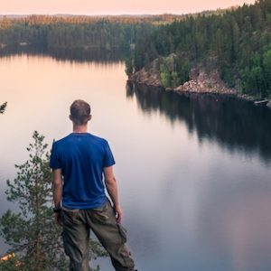 Hiker standing top of the hill front of beautiful idyllic landscape in Mäntyharju, Finland